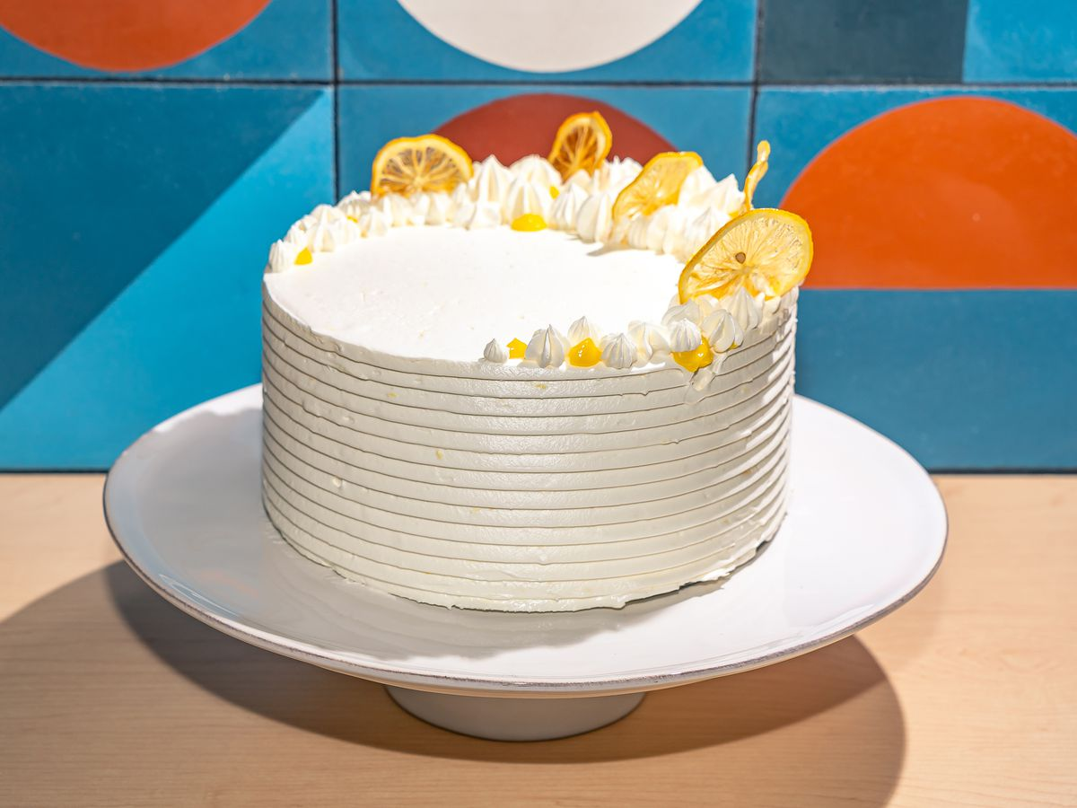 A white cake with slices of lemon propped up on a stand against a colorful background