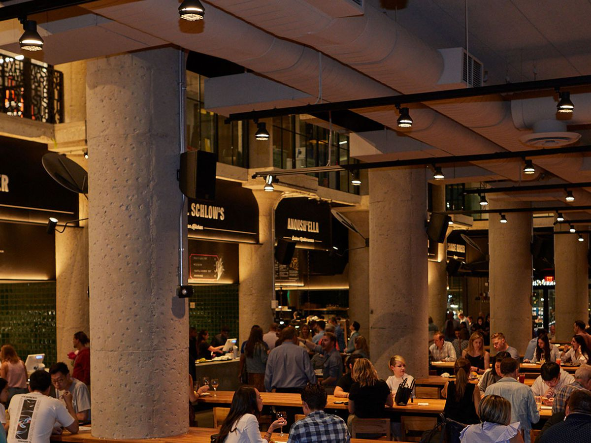 The interior of the Time Out Market Boston food hall, full of large stone pillars, long wooden communal tables, and customers