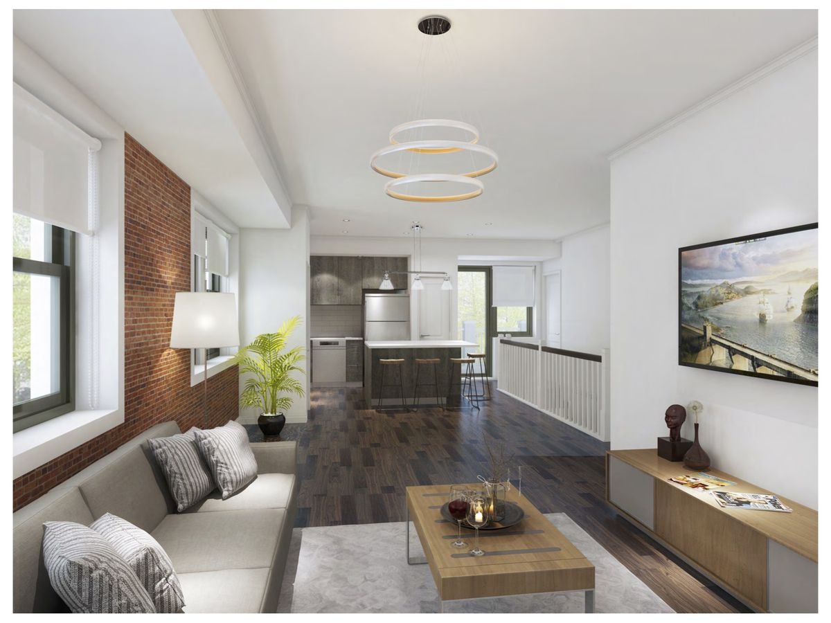 A living room and kitchen in an open floor plan. There's a white-cushioned couch, small wood coffee table, and long wood table against a wall with a painting above it. There's some exposed brick above the couch.