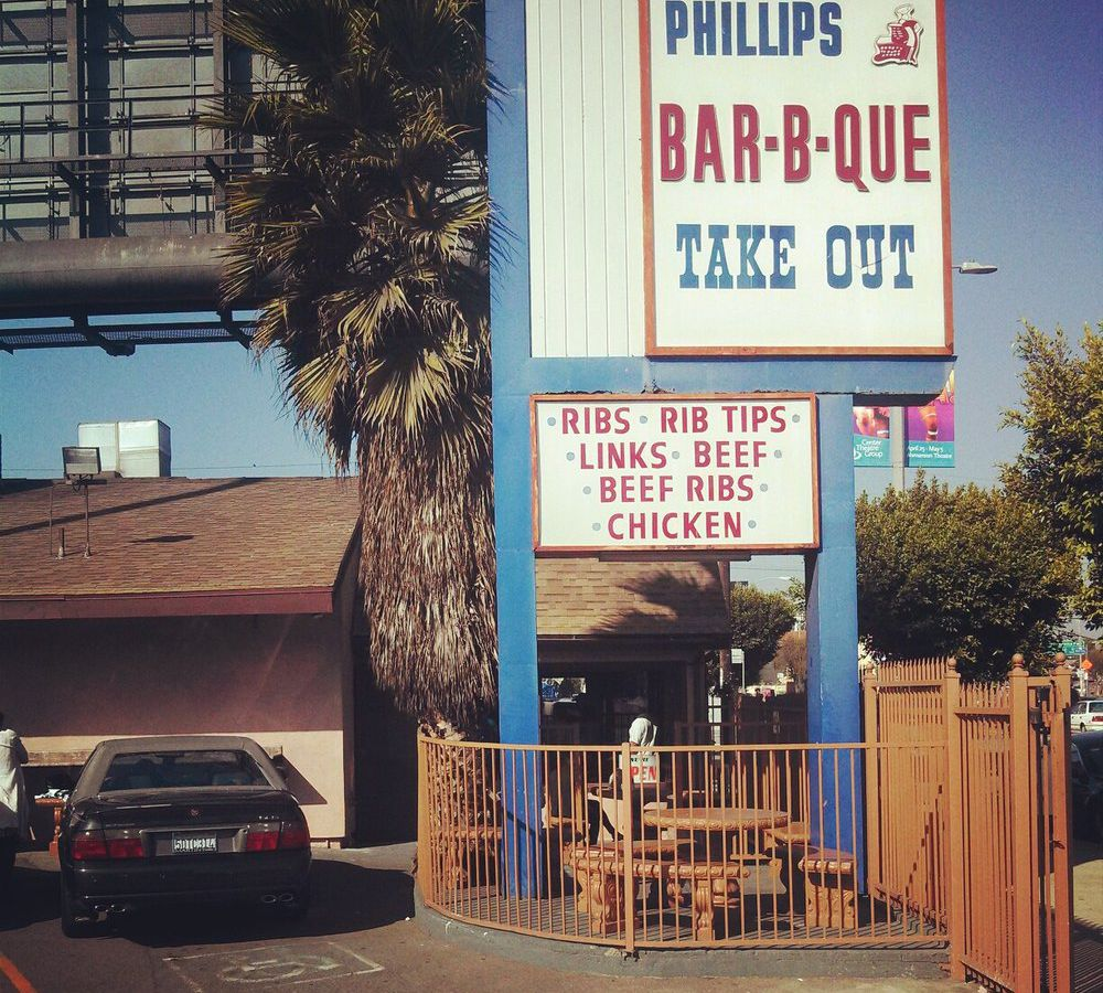 A white and blue sign during the daytime for Phillips Barbecue.