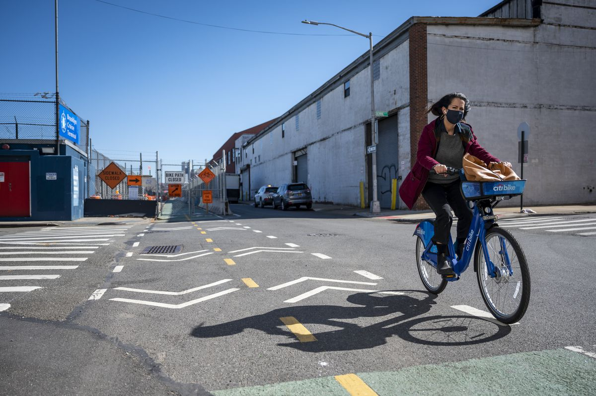 A cyclist swerves back onto the bike path after a stretch of greenway interrupted by construction barriers in Brooklyn.