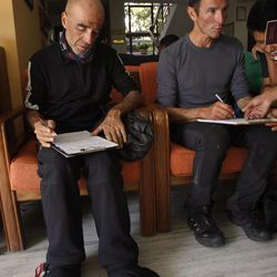 French national Claude Belmas, 52, left, and Armand Manel, 42, survivors of an avalanche at Mount Manaslu in northern Nepal, give their details at a clinic in Katmandu, Nepal, Sunday, Sept. 23, 2012. The avalanche swept away climbers on a Himalayan peak in Nepal on Sunday, leaving at least nine dead and six others missing, officials said.