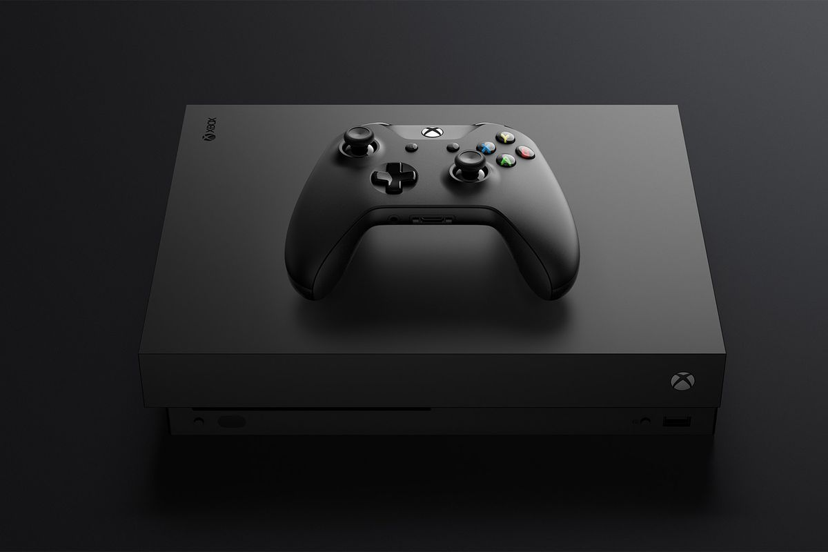 A photo of an Xbox One X console with an Xbox One controller resting on it top panel.