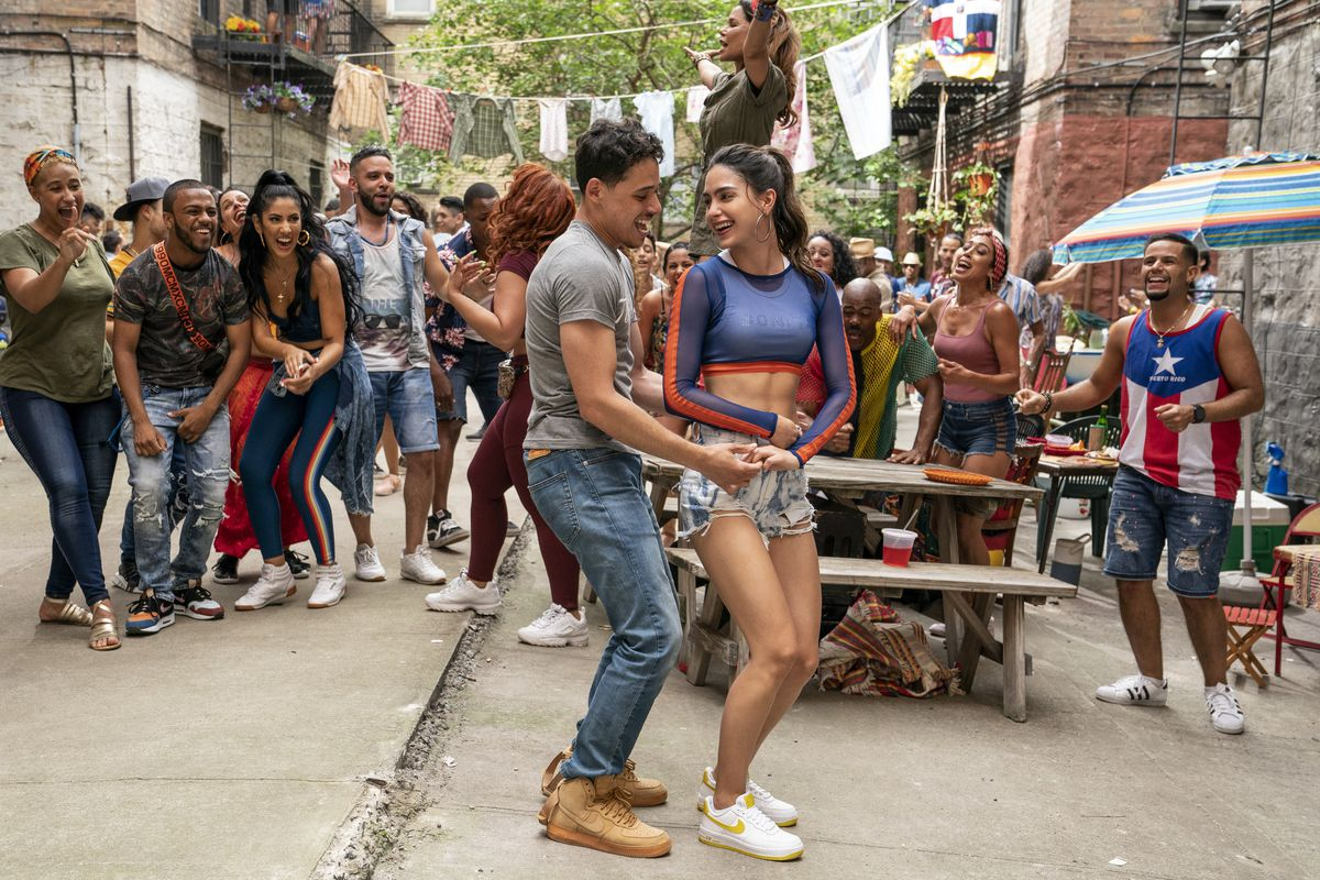 a man and woman dance in front of a picnic table as their friends cheer them on in In the Heights