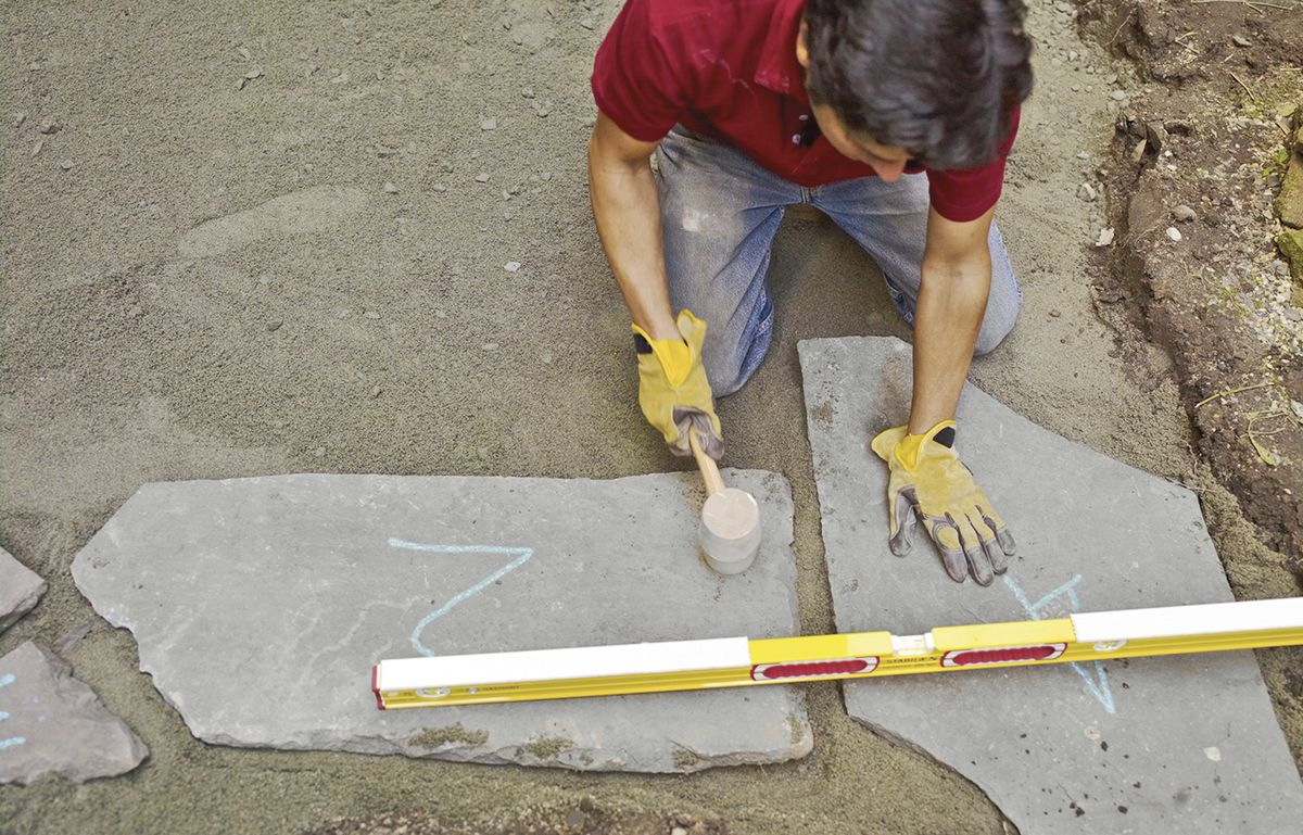 Man Levels Stone For Bluestone Patio