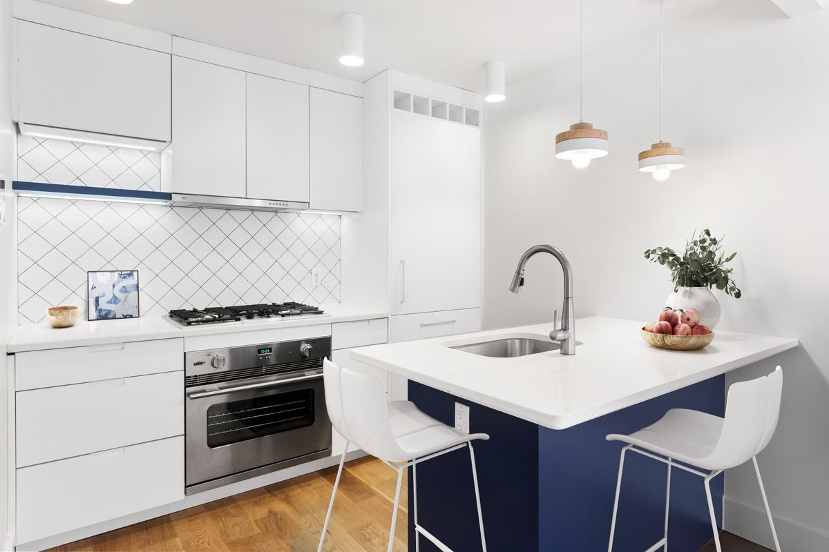 A kitchen with white cabinetry and an island with high top chairs.