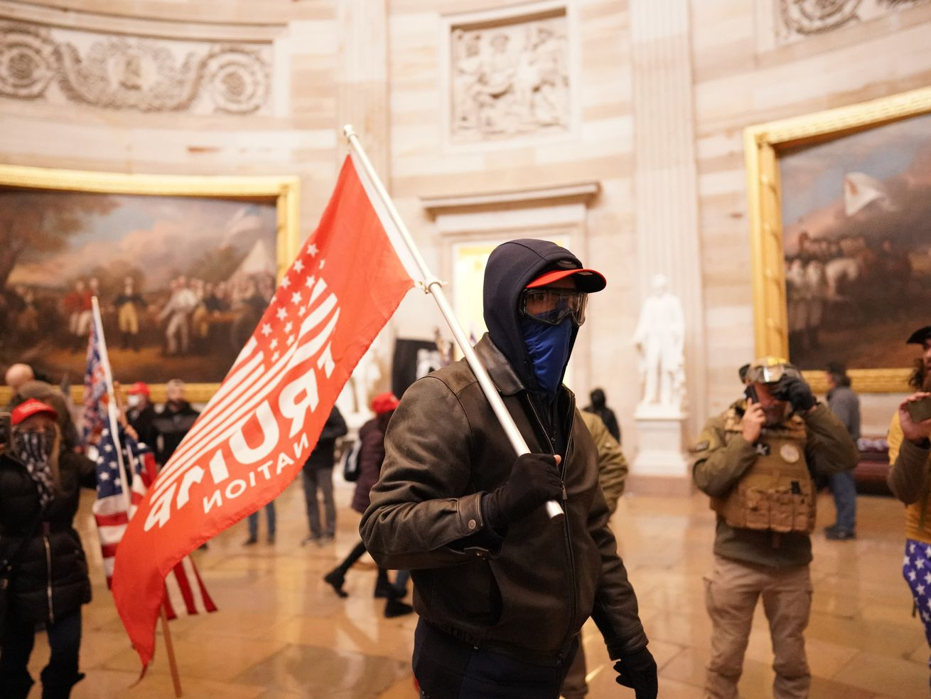 Protesters in a chamber of the Capitol in Washington, D.C. One holds a Trump flag in the center of the image.