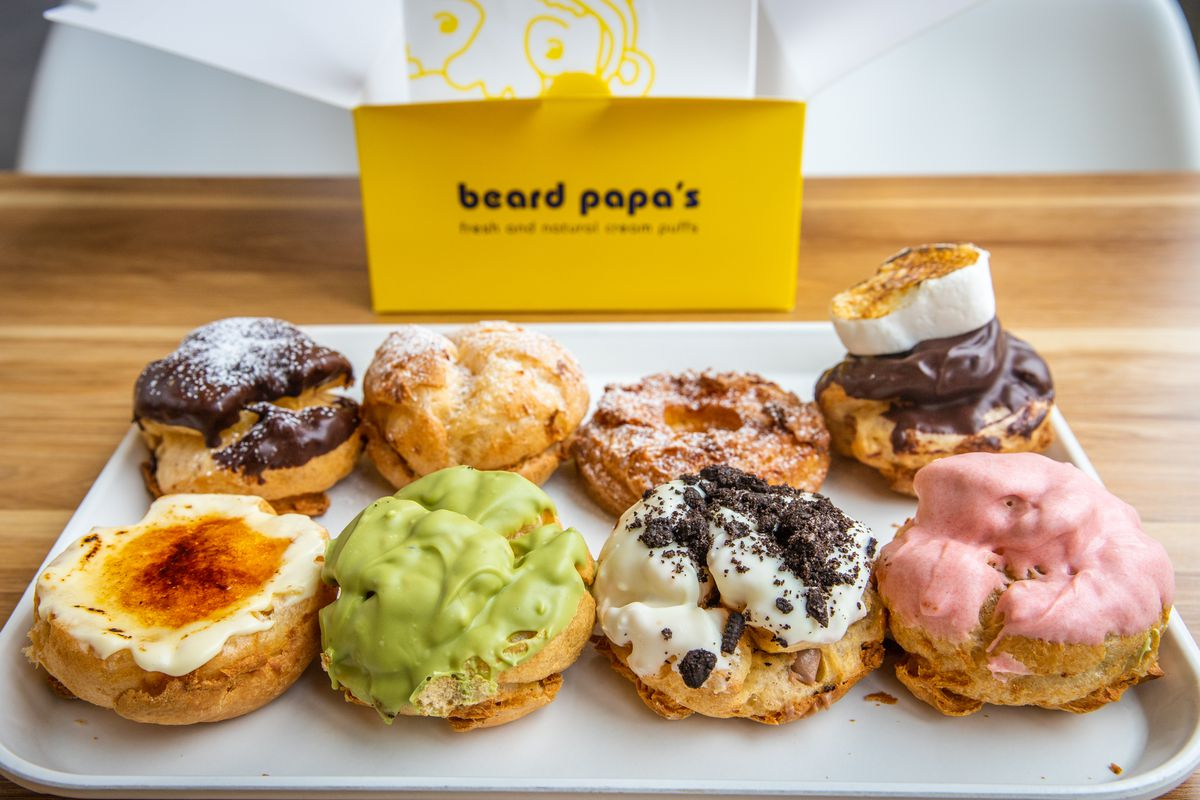 A selection of eight different colors of cream puffs topped with various icings.