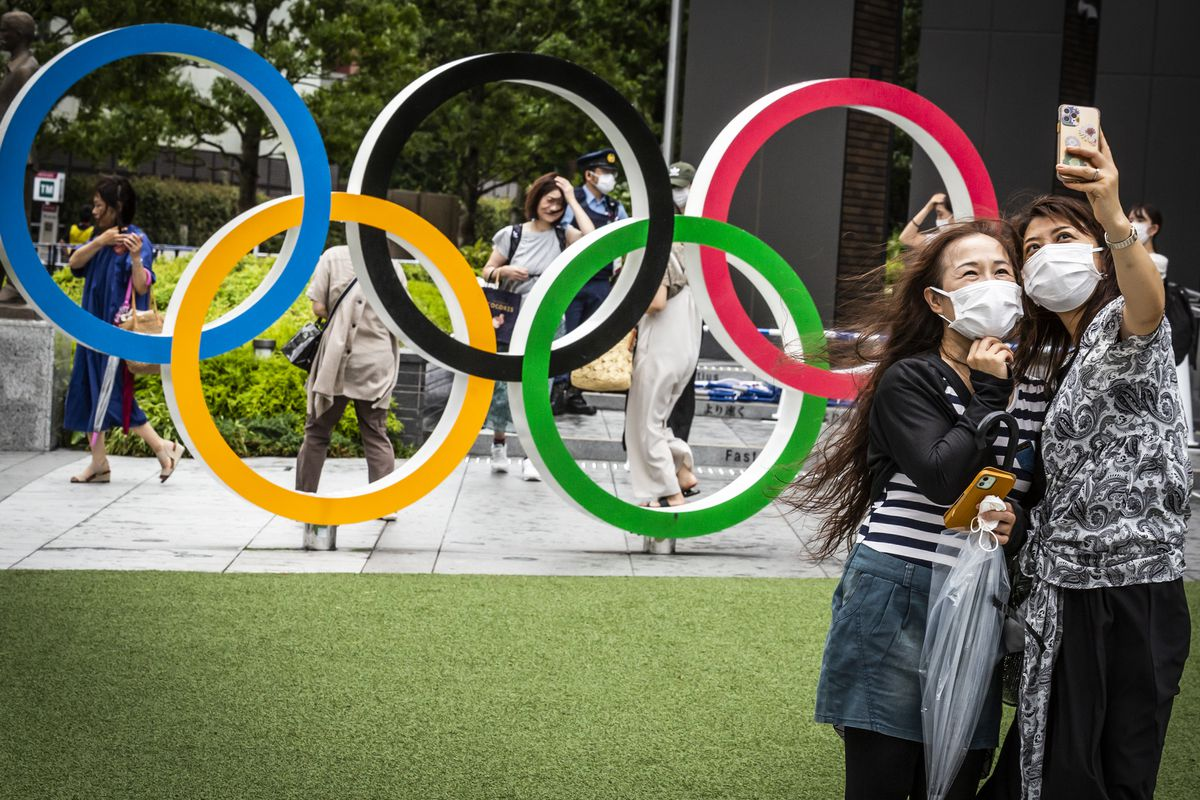 Two masked people take a selfie in front of the Olympic rings.
