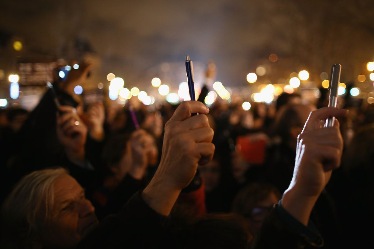Attendees at a Paris rally hold up pens in support of Charlie Hebdo