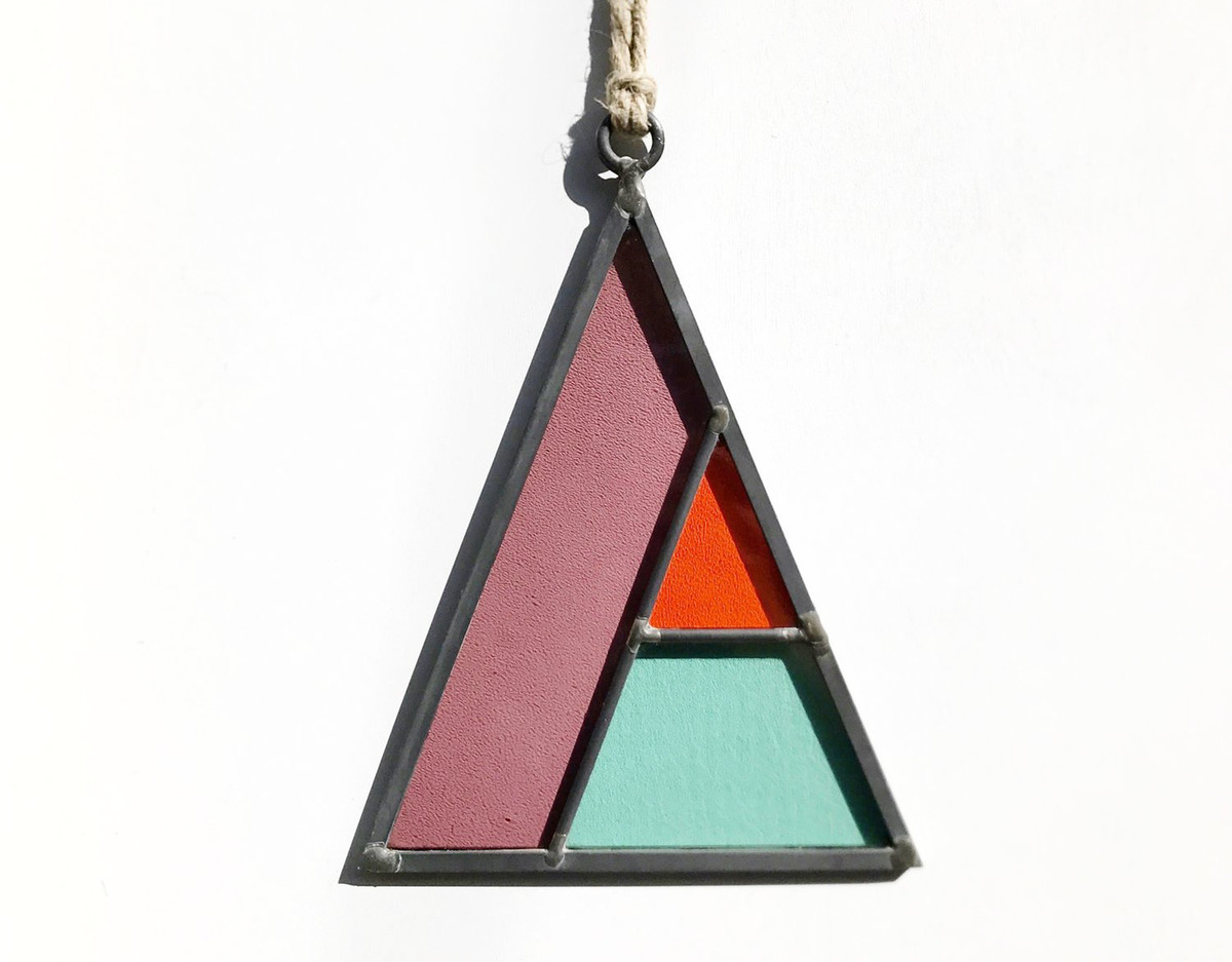 A multicolor stained glass object on a necklace. The object is shaped like a triangle with red, blue, and purple panes of glass set within black framework.