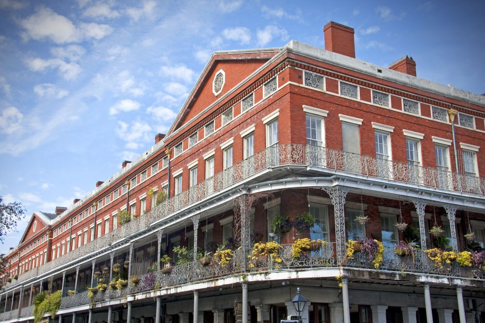 The exterior of the Pontalba buildings in New Orleans. The facade is red and there is a balcony on the upper level with flowers and plants hanging on the balcony edge.