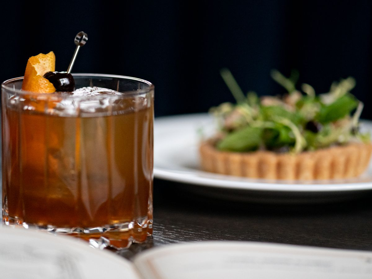 A picture of an Old Fashioned in a low, crystal glass, with a savory tart behind it on a plate