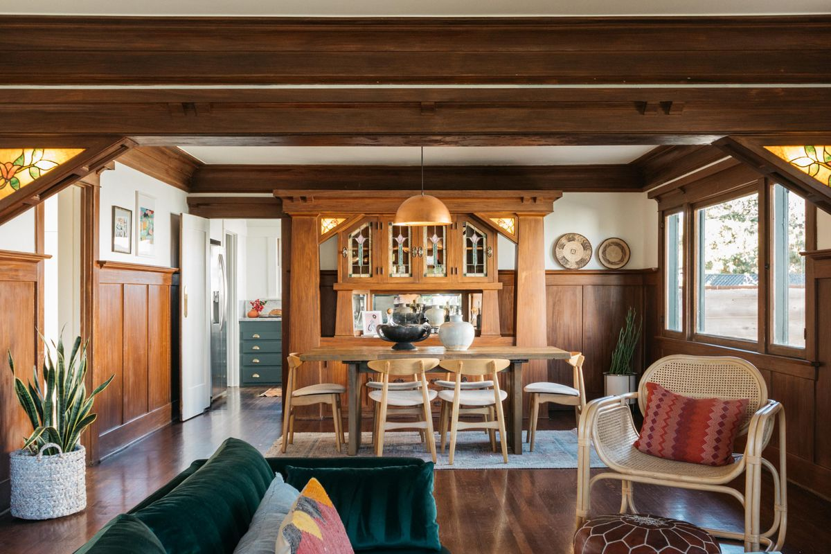 A dining room with built-in wooden cabinet and wood paneling.