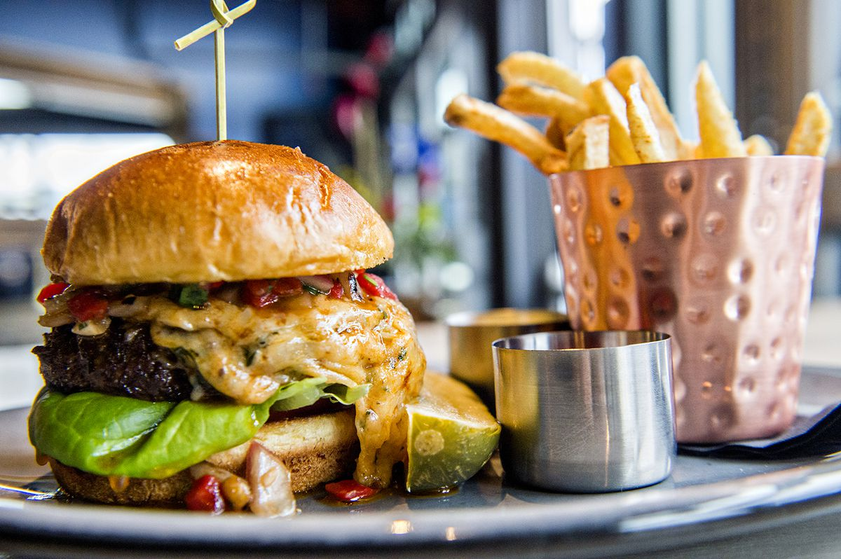 The Pistol Whip Burger topped with pimiento cheese, butter lettuce, heirloom tomatoes, grilled onion relish and Texas Pete sauce served with garlic fries.