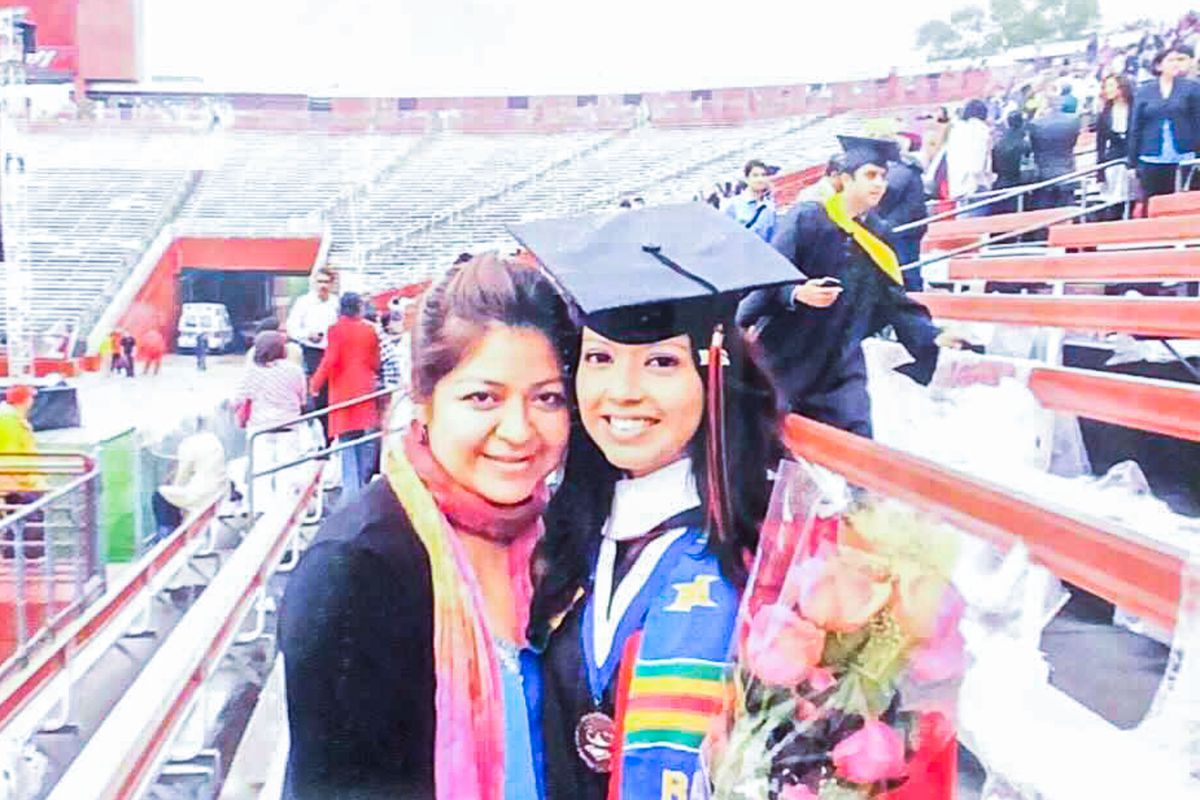 Chalkbeat Newark Bureau Chief Catherine Carrera  wears a black graduation cap and multicolored sash while posing with her mother at her college graduation.