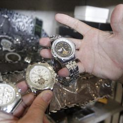 """This Oct. 17, 2012, photo shows Rob Olson of Erkelens & Olsen Auctioneers displaying Rulon Gardner's watches at his auction house, in Salt Lake City. The auction of Olympic gold medalist Rulon Gardner's most valuable belongings is being postponed indefinitely as the decorated wrestler tries to buy back """"stuff that really matters to him,"""" his new bankruptcy lawyer says. A major creditor seized a Ford Excursion SUV, Harley-Davidson motorcycle, dozens of watches and knives, his wrestling shoes, autographed memorabilia and more. Gardner's gold and bronze medals are not in play; he previously put them up as collateral for personal loans. (AP Photo/Rick Bowmer)"""