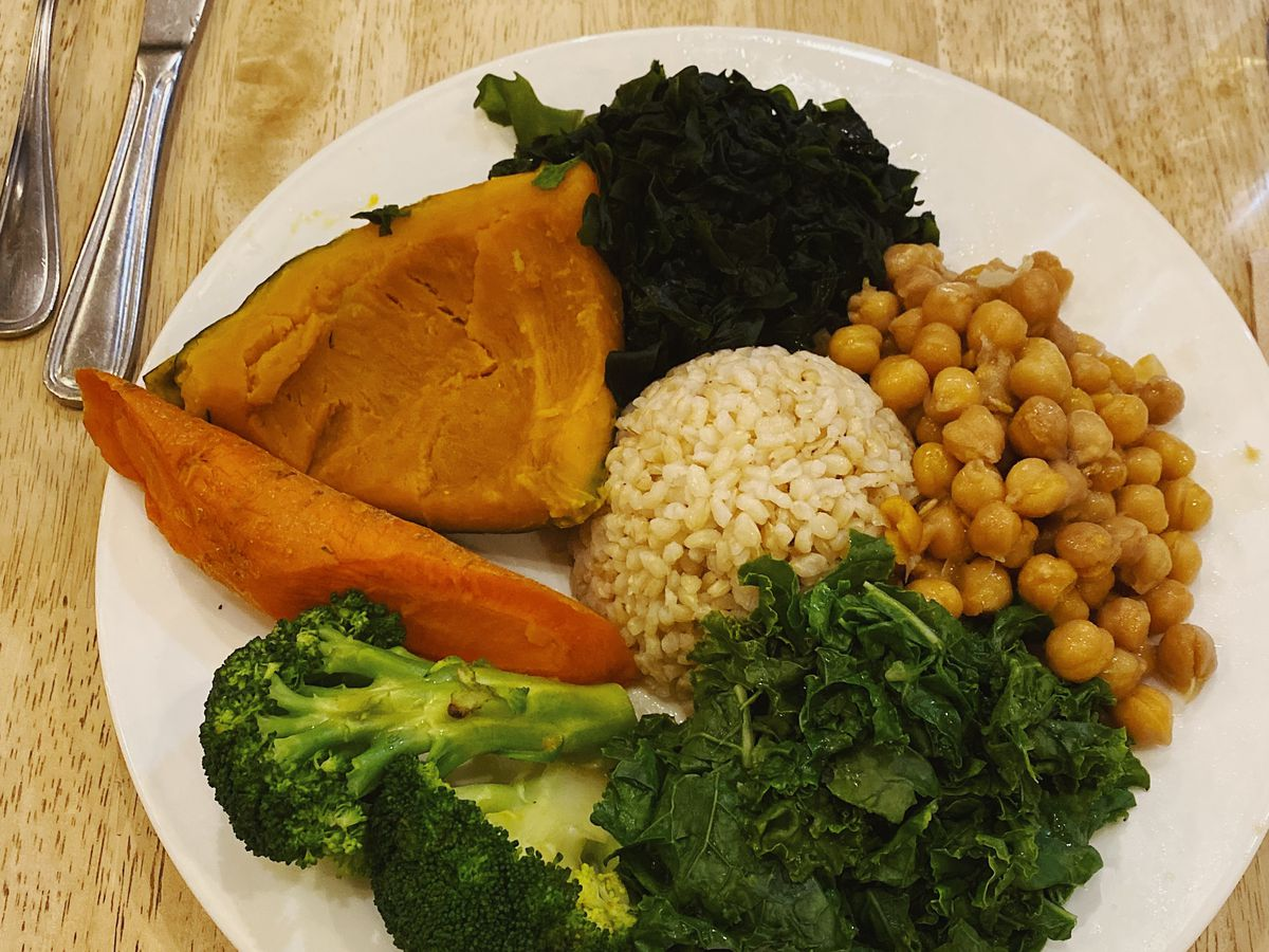 A white plate composed of green vegetables, and red lentils