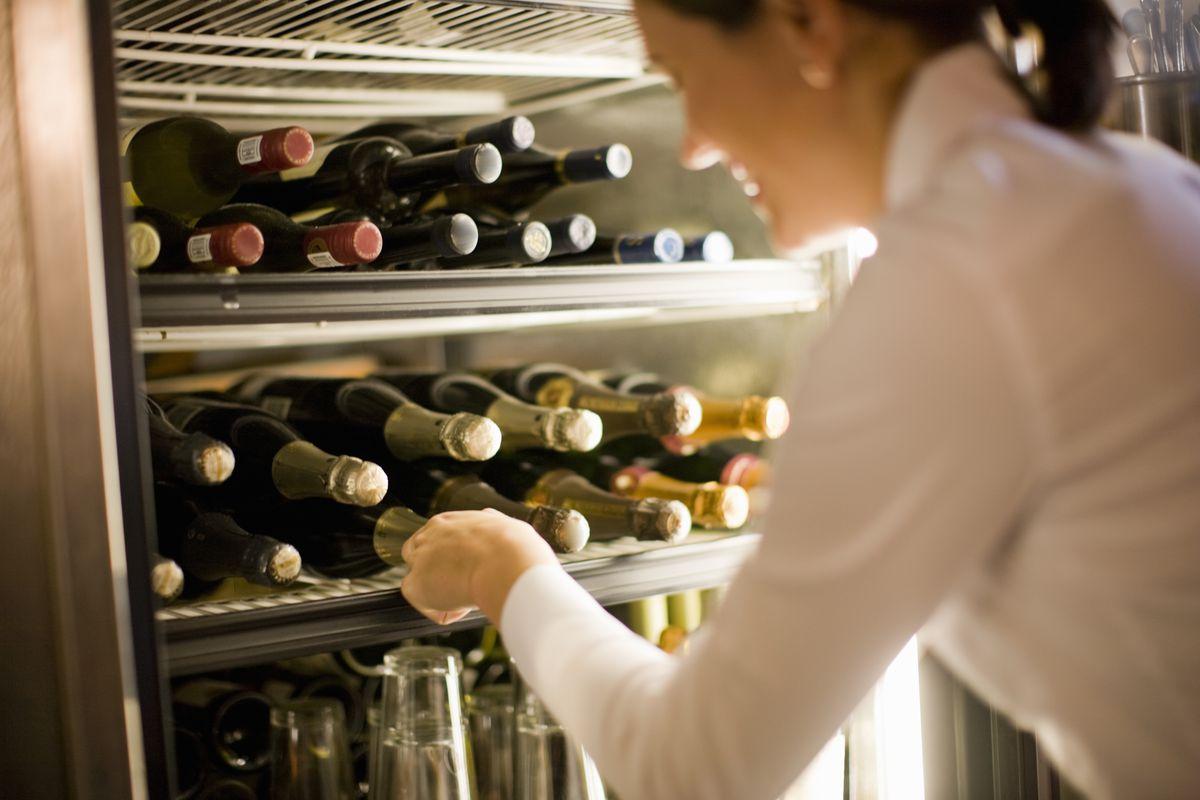 Woman in white crisp professional shirt pulling wine bottle from fridge full of wine bottles