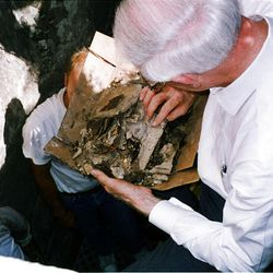 Elder Loren C. Dunn of the Quorum of the Seventy examines fragments of books, pamphlets and periodicals retrieved Aug. 13, 1993, from the Salt Lake Temple record stone. Elder Dunn is above the hole in the ground that was dug beside the temple.