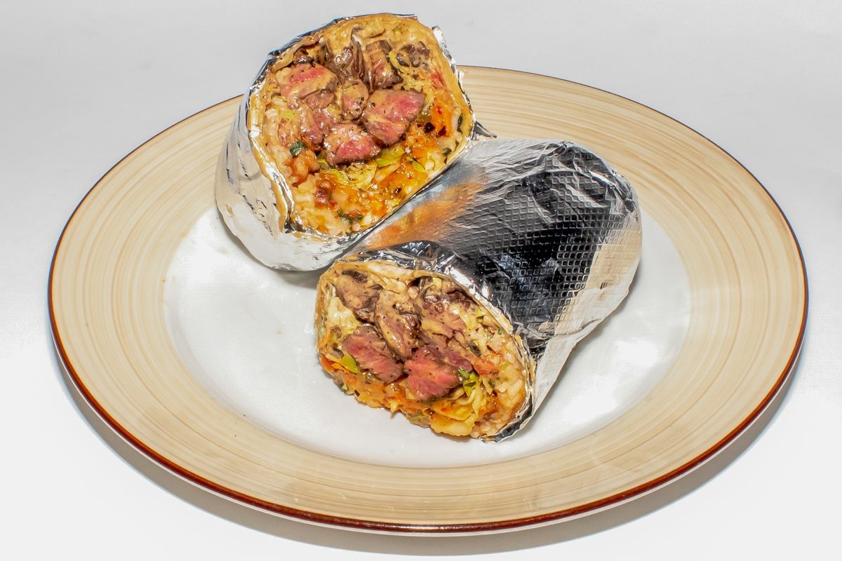 Two halves of a burrito wrapped in aluminum foil sit on a beige plate against a white background