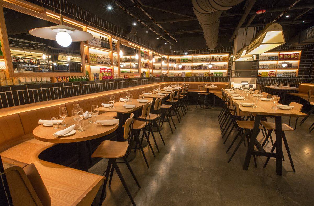 A tapas restaurant with lots of light colored woods, black tiles and more.