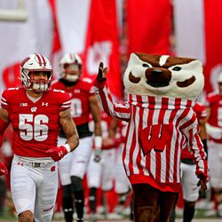Zack Baun and Bucky Badger lead UW onto the field before the Iowa game. It was the 92nd game between the two schools.