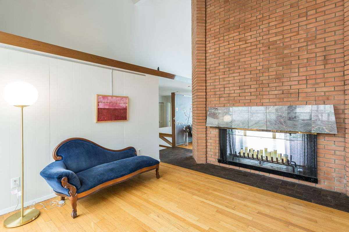 A brick fireplace has candles where the fire goes and a blue day bed on the left.