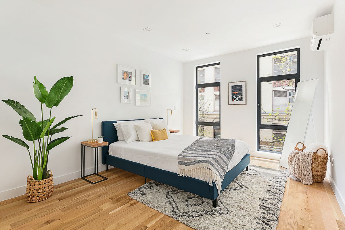 A bedroom with a small bed, a planter, hardwood floors, and two floor-to-ceiling windows.