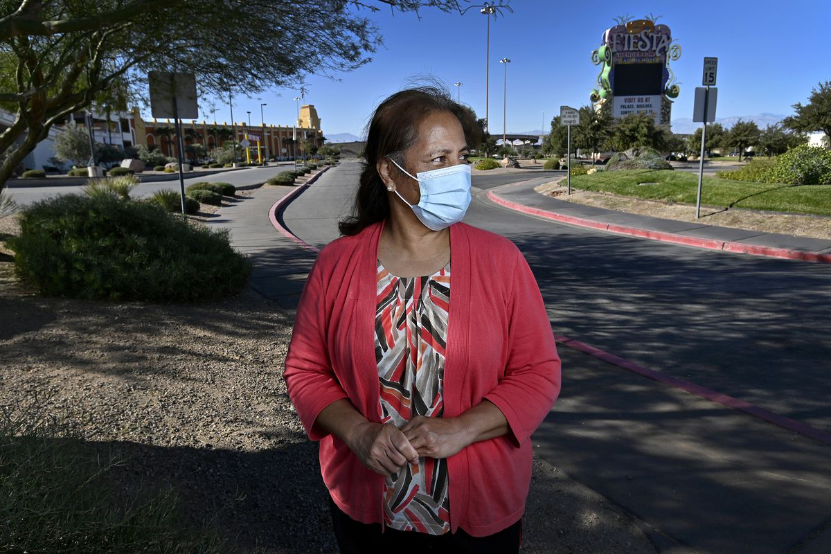 Luceanne Taufa poses at the still closed Fiesta Henderson Hotel & Casino on Saturday, Nov. 21, 2020, in Henderson, Nev. Taufa was laid off after the casino was forced to shut down when the governor issued a statewide mandate in March due to the coronavirus pandemic and has yet to reopen for business.