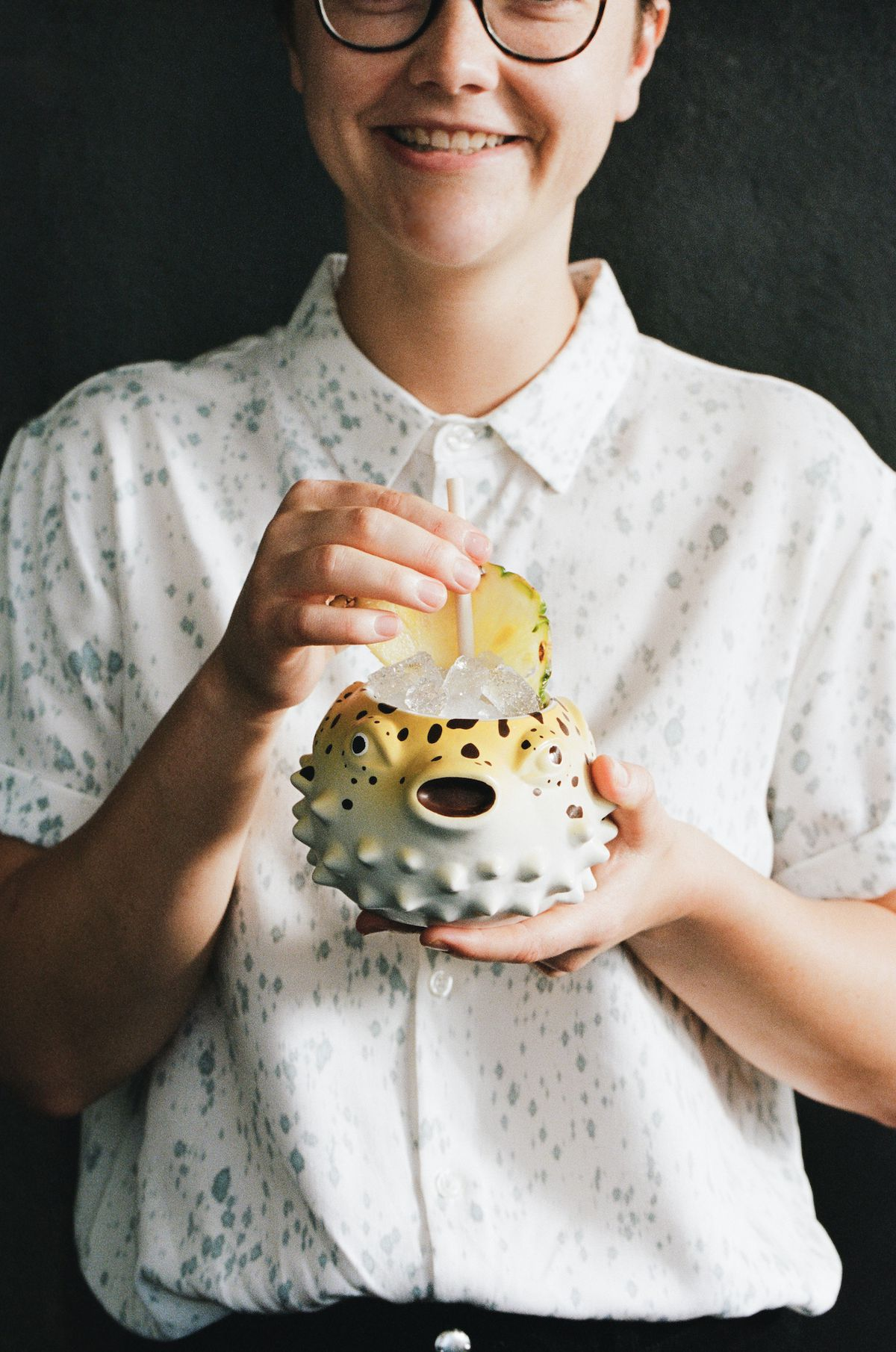A worker in glasses holds a funky punch bowl cocktail glass that looks like a blowfish.
