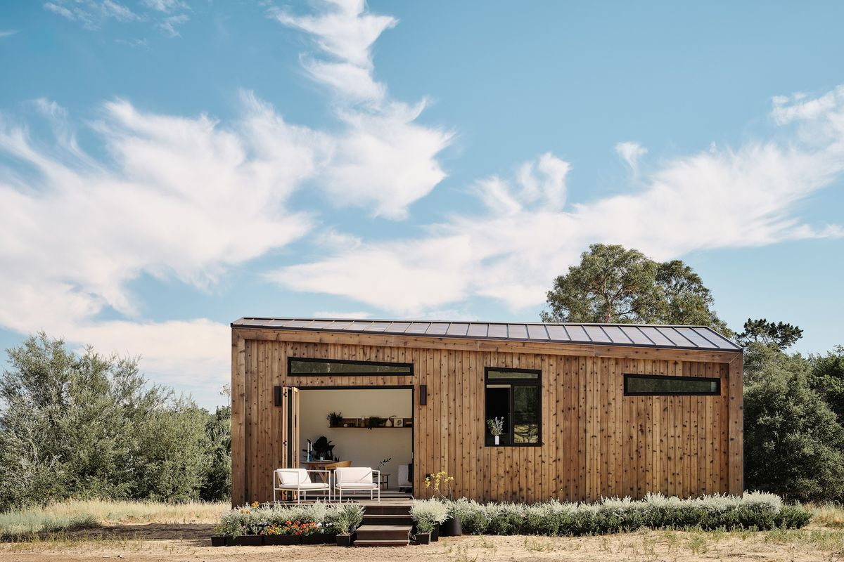 A small wood-clad prefab home with slanted roof sits on grassy plot.