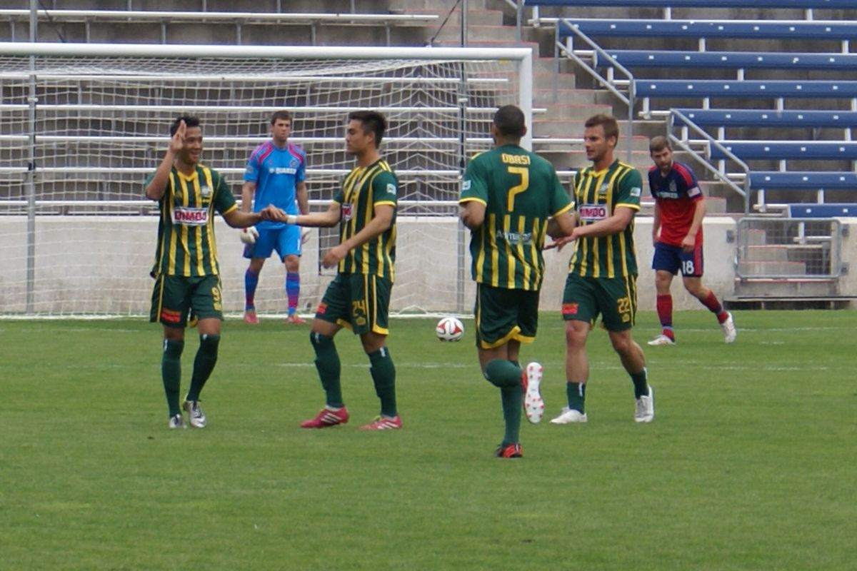 Minh Vu celebrates with his teammates after scoring the game's opening goal