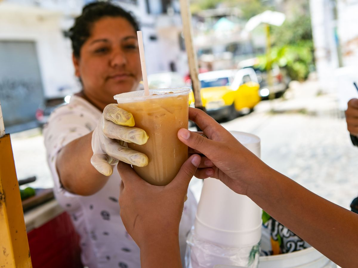 A woman in a glove hands another hand a cup of brown liquid on ice.
