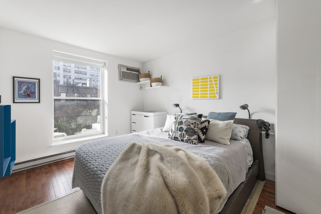 A bedroom with a large bed, white walls, a floor-to-ceiling window, and hardwood floors.