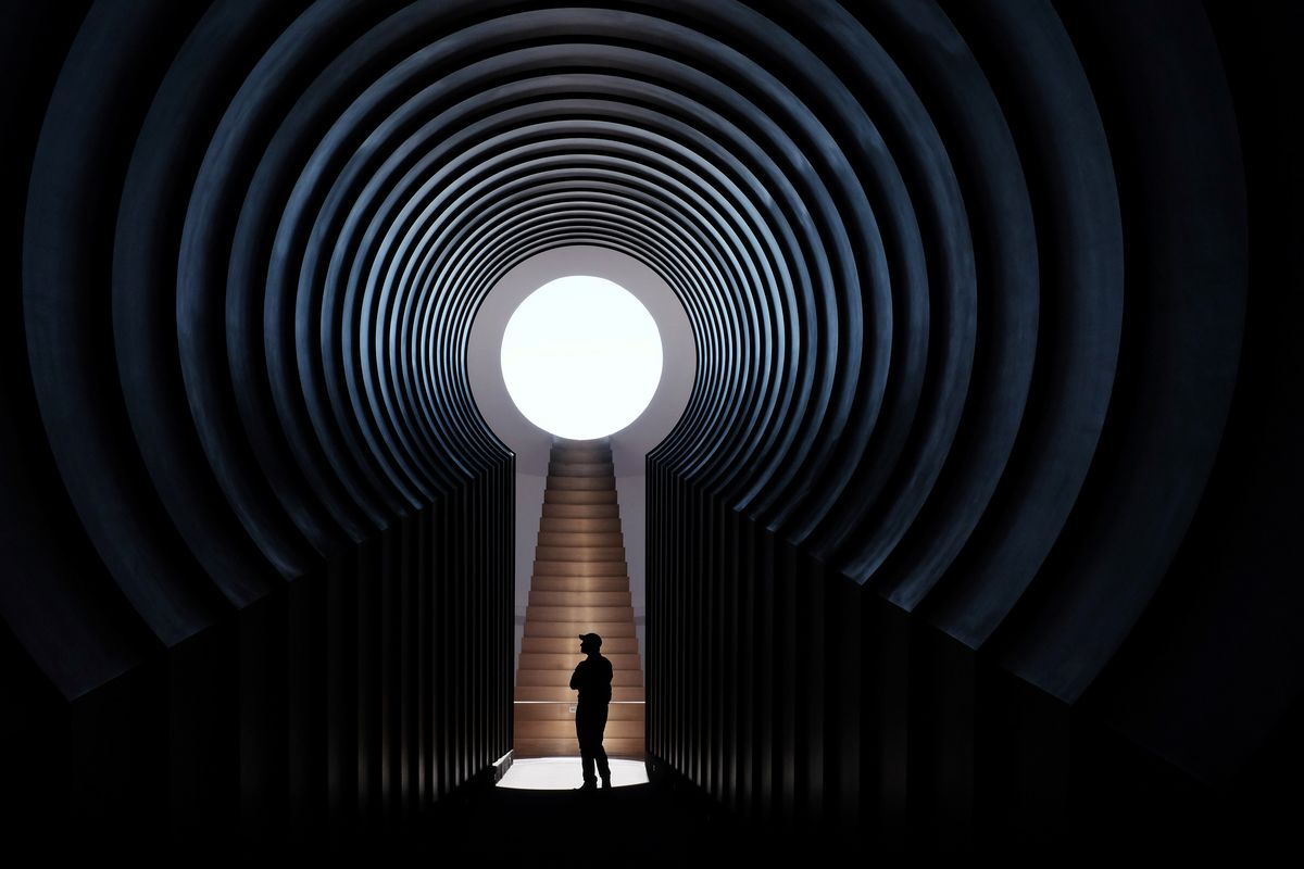 A man is silhouetted against a circular window within a series of receding arches.