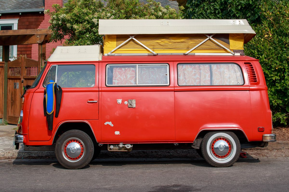 A parked bright red VW camper van with a wetsuit hanging from the driver's side mirror.