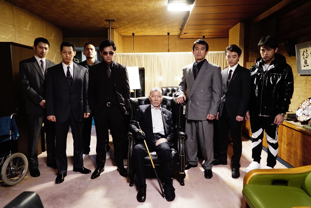 A group of men in suits gather facing the camera.