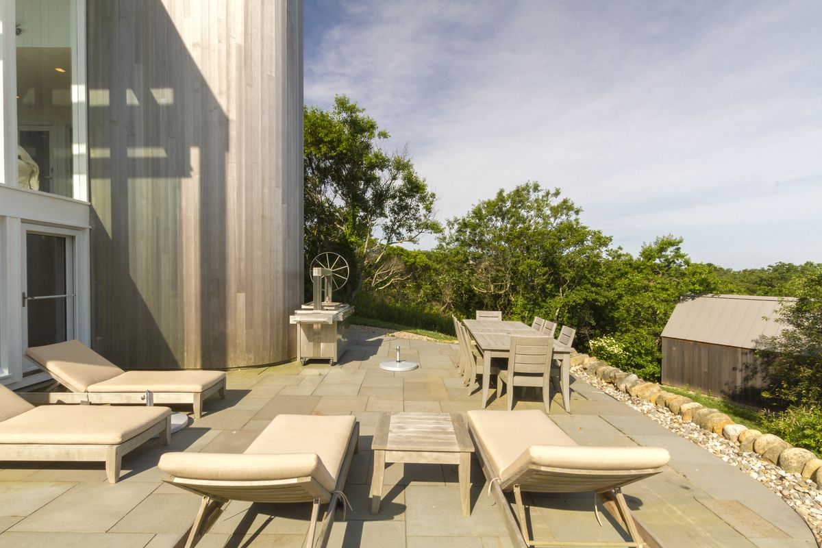 A stone patio off of the home's living room features four beige lounge chairs and an outdoor dining set.