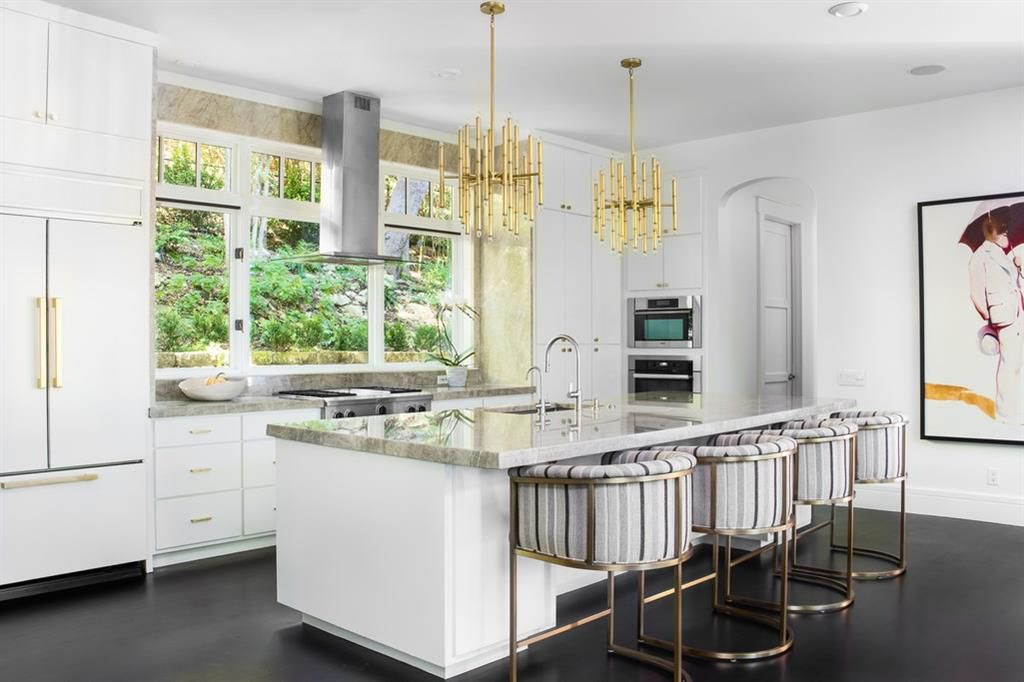 An closer view of the open kitchen with a breakfast bar island. There are two modern chandeliers over the island and four horseshoe-shaped, cushioned bar stools in front. The back counter has a stovetop in the middle, a triptych of windows on the wall, cabinets and drawers below, and floor to ceiling cabinets on each site. The left side has a refrigerator designed with the same finish as the cabinets. There's an inset microwave and oven on the wall adjacent to the right of the tall cabinets.