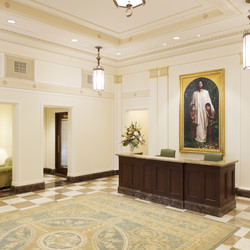 A view of the redesigned front entrance (west side) of the Mesa Arizona Temple with artwork of the Savior Jesus Christ as the central focus. Dark walnut finishes, checkerboard marble flooring from Turkey and Spain, and marble wainscot and base from the original quarry in Birdseye, Utah, help bring back the authentic Colonial Revival décor of the 1920s.