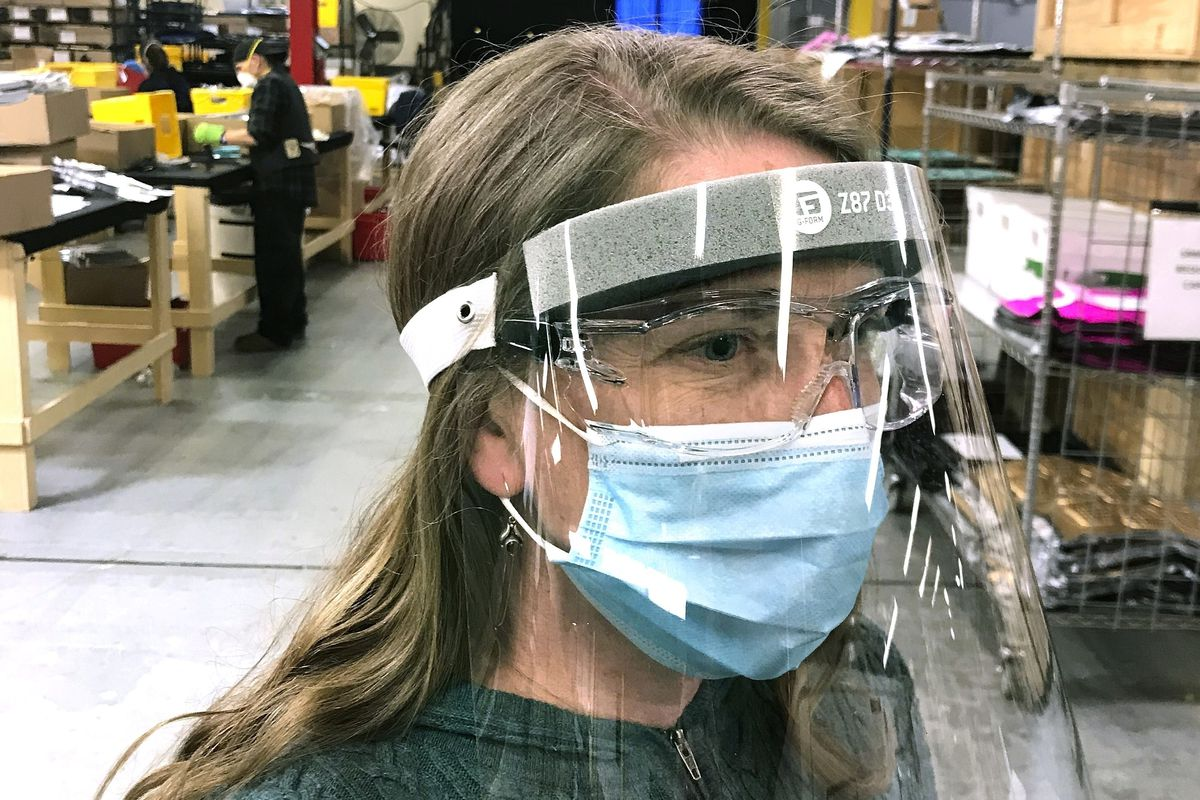 In this photo provided by G-Form, a worker wears one of the shields the company is producing at its factory in Smithfield, R.I. The company has retooled from making protective sports gear to making face shields for medical personnel.