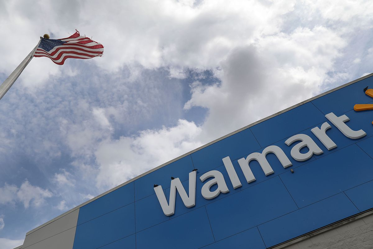 A Walmart sign with an American flag flying above it.