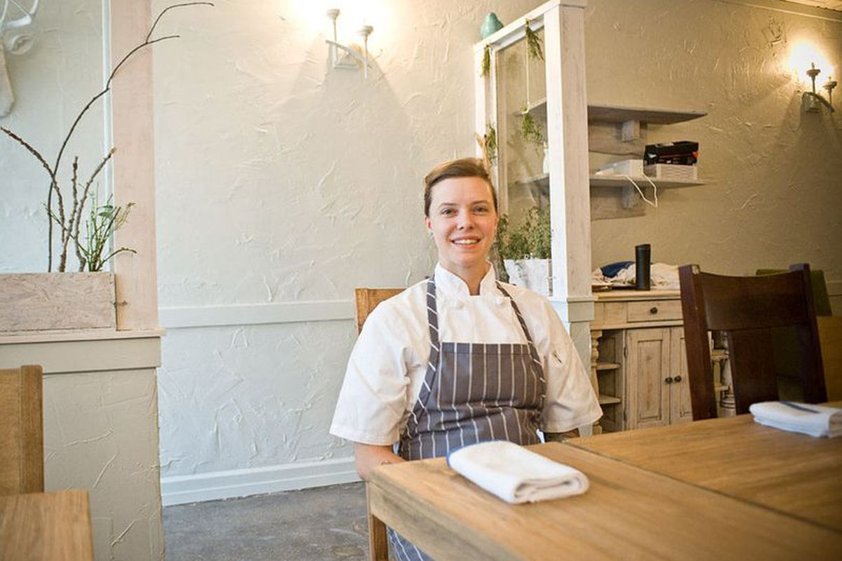 A white female chef sits at a wooden table in a dining room.
