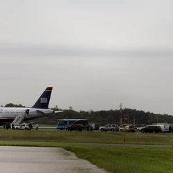 """Emergency personnel look over a US Airways plane at Philadelphia International Airport, after the plane returned to the airport, Thursday, Sept. 6, 2012, in Philadelphia. Airport spokeswoman Victoria Lupica says US Airways Flight 1267 returned to the airport Thursday morning as a """"precaution.""""   Footage from WCAU-TV showed a person being escorted off the plane by law enforcement officials and police dogs on the tarmac. An FBI spokesman did not immediately comment on the situation."""