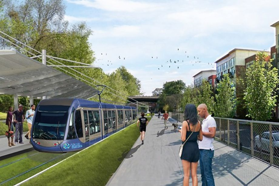 Shown in renderings is a hypothetical train stop with grass and several people exercising.