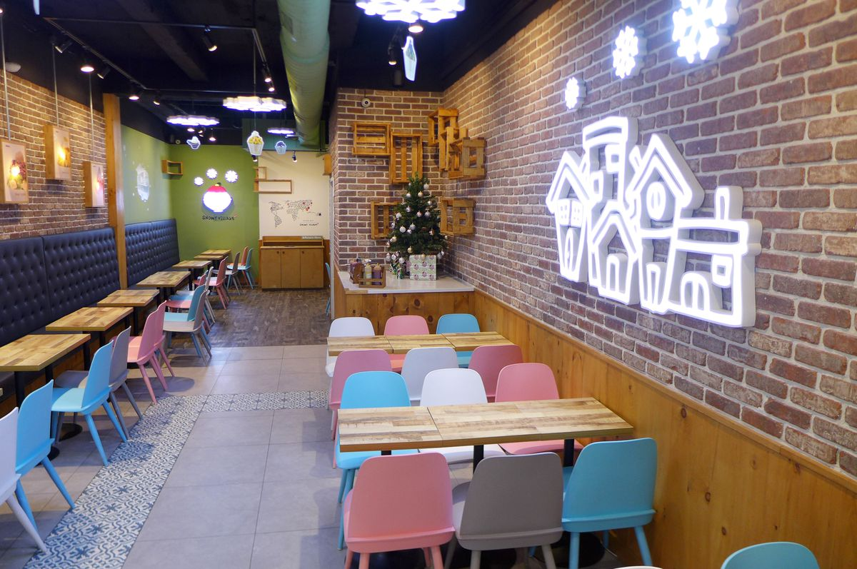 A brick restaurant interior with pastel furniture and a lit up snowy village on one wall.