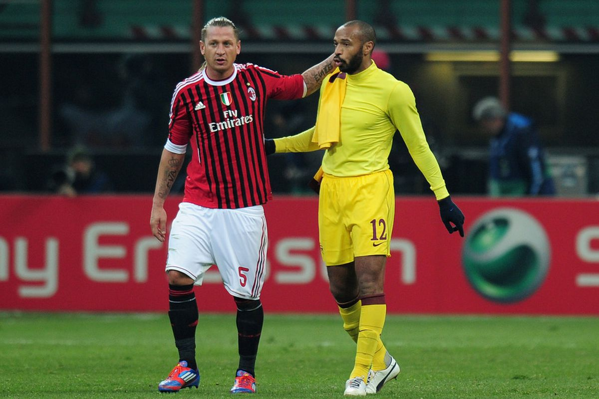 Thierry Henry of Arsenal is consoled by Philippe Mexes of AC Milan after the UEFA Champions League round of 16 first leg match at Stadio Giuseppe Meazza on February 15, 2012 in Milan, Italy.