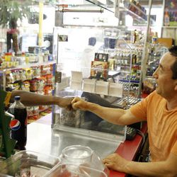 In this Friday April 20, 2012 photo, James Oh, right, owner of Tom's Liquor on the corner of Florence and Normandie, greets a customer in his store in South Los Angeles. In the 20 years since the 1992 riots, residents of the city's largely black and Hispanic South Side complain that the area still is plagued by too few jobs, too few grocery stores and a lack of redevelopment that would bring more life to the area.