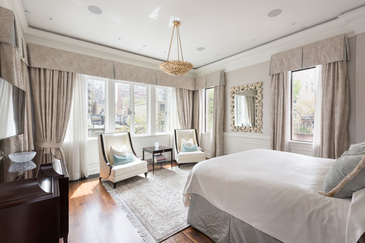 A bedroom with wall moldings, beige curtains, and a medium-sized bed.